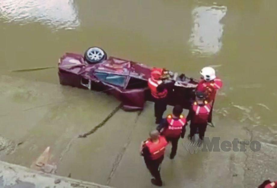 ANGGOTA bomba menjalankan operasi menaikkan kereta yang terjunam ke dalam sungai. FOTO ihsan bomba