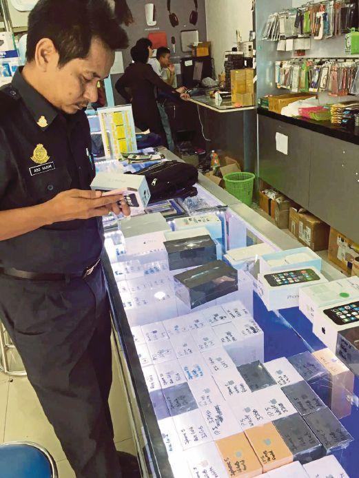 ANGGOTA polis memeriksa gajet tiruan yang dijual kepada orang ramai.