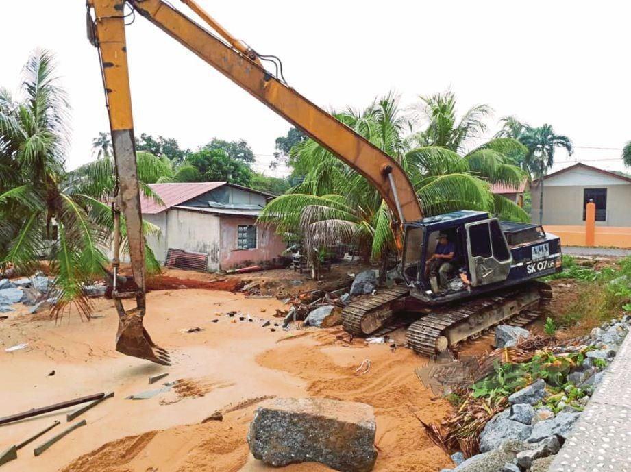 KERJA membina tembok menghalang ombak di Kampung Balik Batu, Tanjung Bidara.