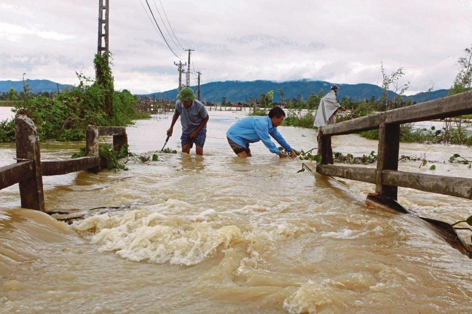 DUA lelaki meranduk air banjir di Nghe An, tengah Vietnam. - AFP
