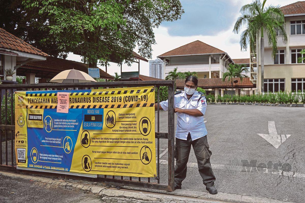 PENGAWAL keselamatan, Parameswary menutup pintu pagar Sekolah Menengah Kebangsaan Bandar Utama Damansara. FOTO Bernama