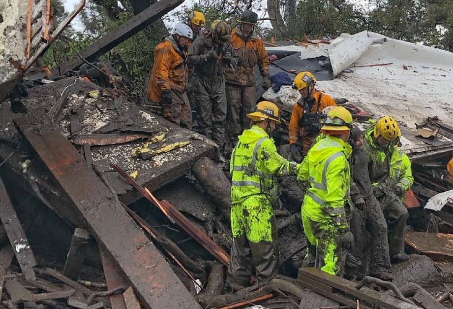 Anggota bomba menyelamatkan remaja perempuan 14 tahun dari rumah yang  musnah di Montecito. - Foto Daily Mail