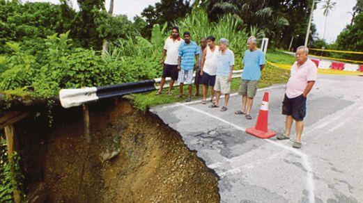 Penduduk kampung melihat tanah runtuh di Kampung Enggor iaitu jalan utama yang menghubungkan jalan besar ke Pekan Karai.