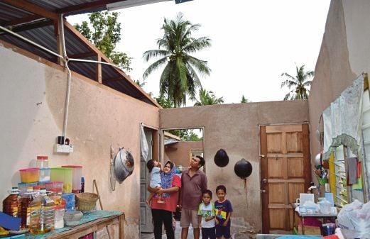 MOHD Ridzuan bersama isteri dan anak berdiri di tengah-tengah dapur mereka yang tidak berbumbung.