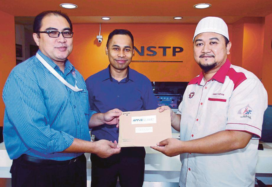 ADI Hanafi (kiri) menyampaikan sumbangan kepada Ahmad Saufuan sambil disaksikan Ketua Biro NSTP Melaka, Badrul Hizar Ab Jabar (tengah) pada Program #HMKotakRezeki2018 di Taman  Melaka Raya, Banda Hilir.