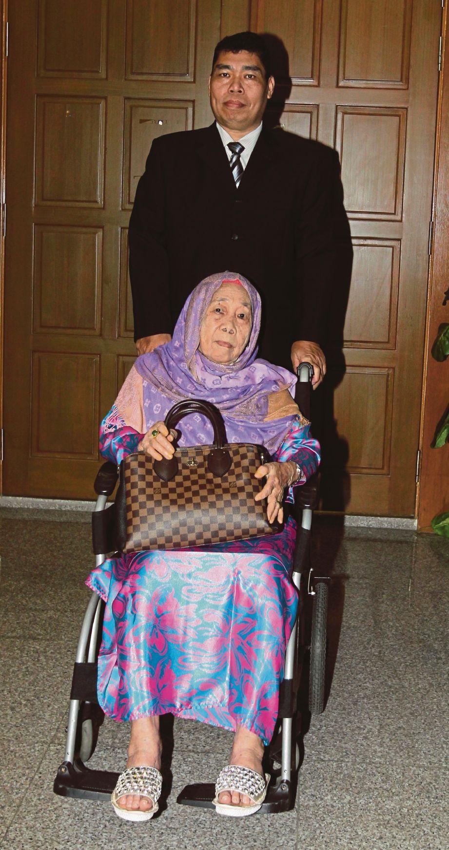 AMINAH (berkerusi roda) bersama anaknya, Mohamad Najeb  ketika memohon sijil faraid tuntutan harta peninggalan Tan Sri Jamaluddin di Mahkamah Syariah Kuala Lumpur.