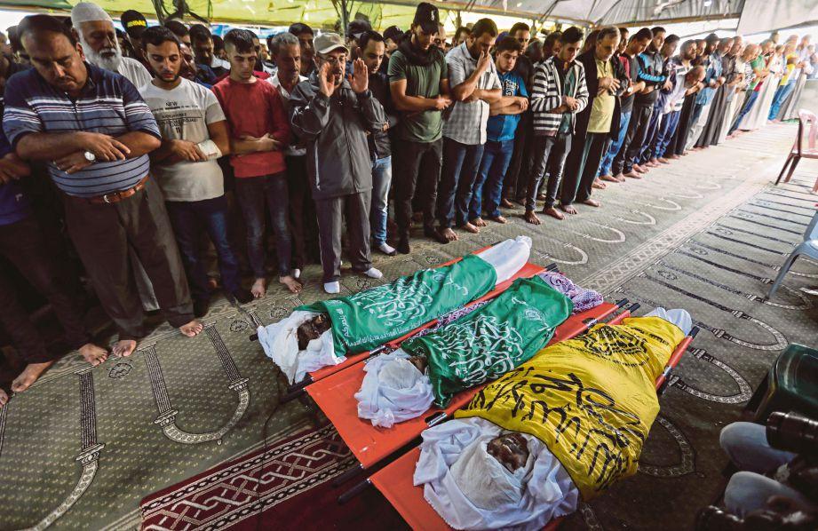 TIGA jenazah korban serangan Israel disembahyangkan penduduk Palestin sebelum dikebumikan di Gaza, semalam. FOTO  AFP