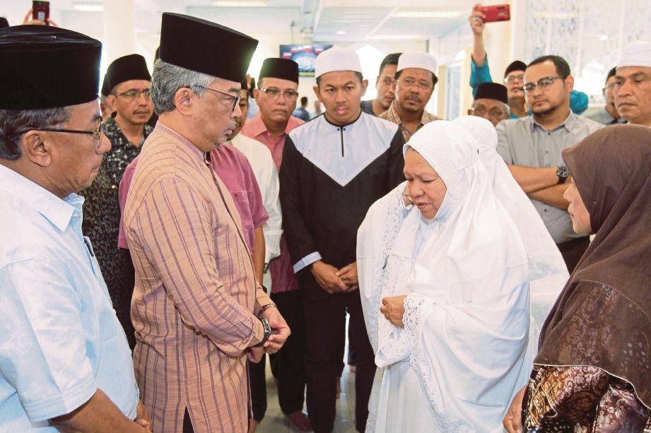 Tengku Abdullah berbual dengan isteri Allahyarham, Rohizah ketika hadir menziarahi jenazah Abdul Manan di Masjid Al-Hidayah, Taman Melawati.
