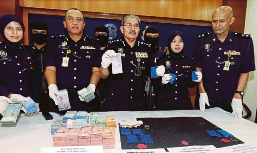 MAZLAN  (tengah)  menunjukkan pil kuda yang dirampas bersama wang tunai  dalam operasi Pasukan Khas Narkotik IPK Kelantan pada sidang media di Kota Bharu.