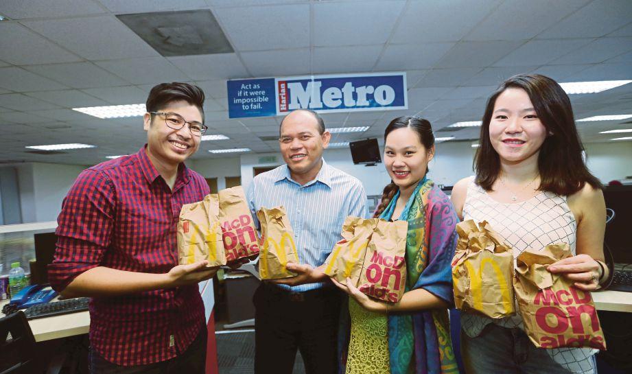 PENGARANG  Bersekutu Rencana Harian Metro, Husain Jahit (dua dari kiri) menerima bungkusan McDonald's daripada Pengarah Urusan VoxEureka, Jonathan Tan (kiri) sempena  McDelivery Day di Balai Berita, The New Straits Times Press (M) Berhad, semalam.
