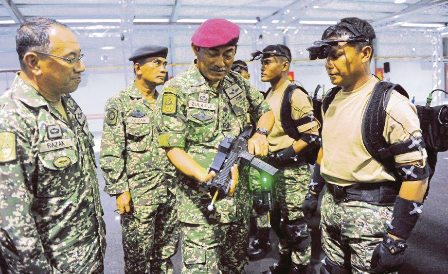 ZULKIPLE (tengah) melihat senjata yang digunakan dalam latihan peperangan Tentera Darat selepas merasmikan sistem VIRTSIM.