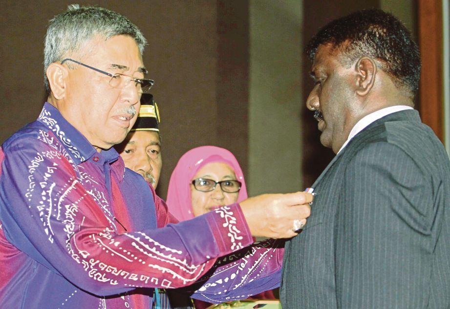 AHMAD Bashah (kiri) menyampaikan anugerah Pingat Setia Sentiasa Berjuang kepada Kapten (Bersara) G Muthusamy, semalam.