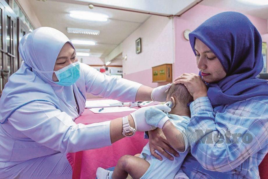 JURURAWAT mengambil bacaan suhu badan pesakit sebagai  saringan awal  mengenal pasti pesakit yang mempunyai risiko dijangkiti Influenza.