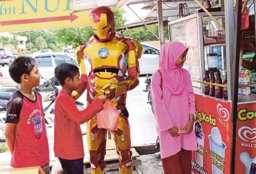 MUHAMMAD Hans melayan pelanggan cilik yang singgah di gerai air coconut shake di Jalan Pintu Geng, Kota Bharu.