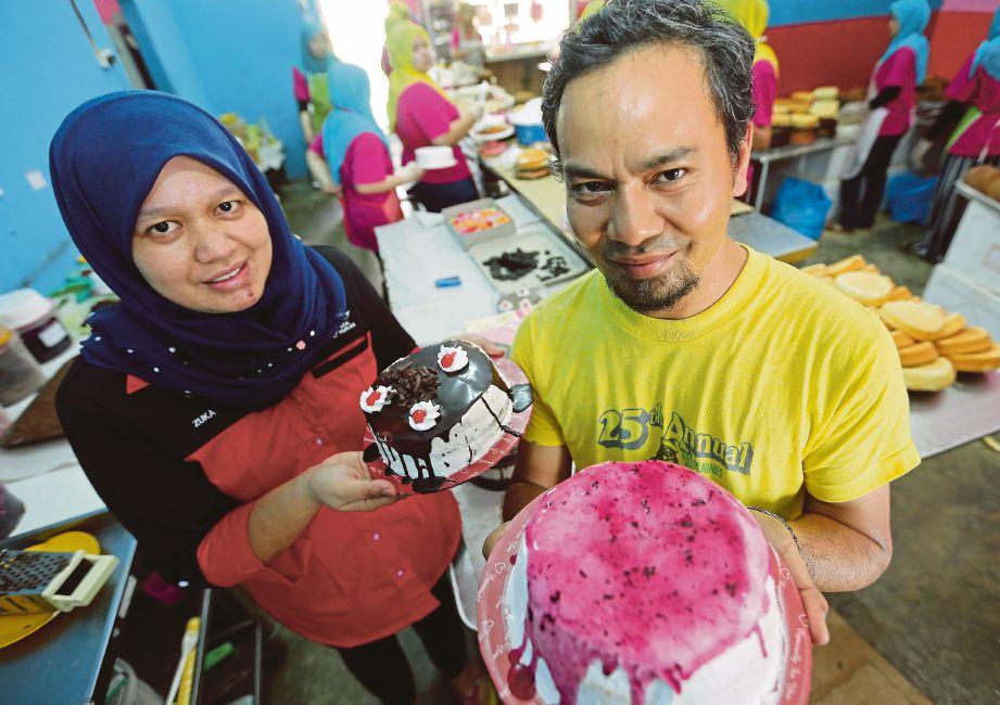 NURUL Hana dan Mohd Nassir menunjukkan kek hari jadi yang dijual.