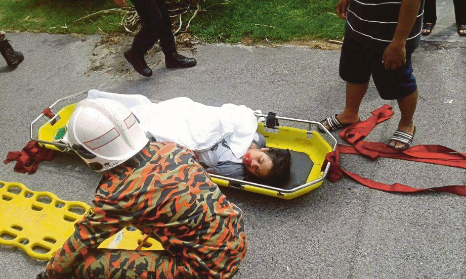 Anggota bomba dan orang awam membantu menaikkan mangsa yang cedera selepas motosikal dinaiki mereka terjunam ke dalam longkang besar di Serdang Jaya, petang semalam.