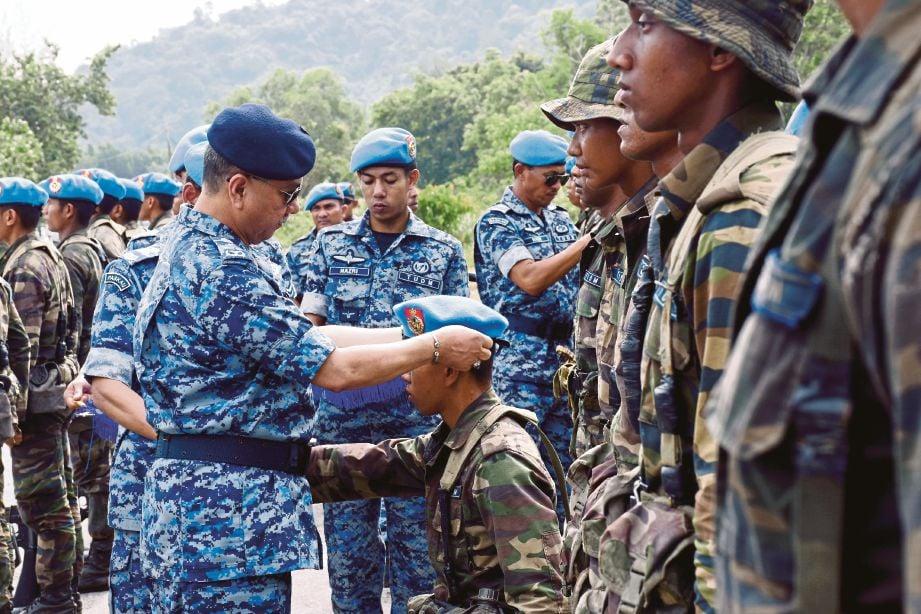 ABDUL Mutalib (kiri) memakaikan beret biru kepada anggota TUDM Malaysia lulus ujian asas komando.