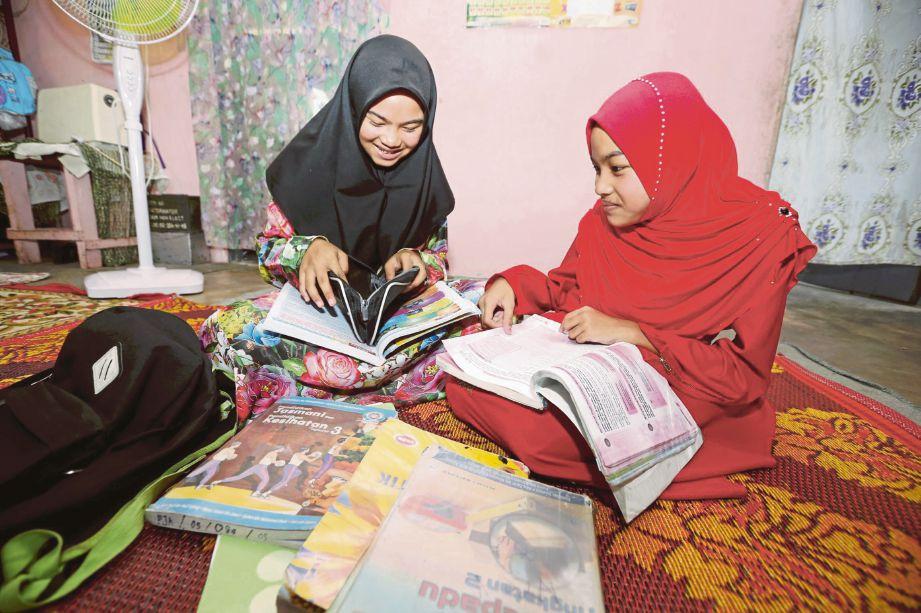 AZAMA (kiri) dan Azami ketika mengulang kaji pelajaran di rumah keluarga mereka di Padang Luas Dalam, Besut.