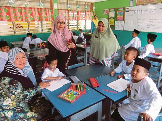 Norizan  (kiri)   menemani  Mohammad Raeez     di dalam kelas setiap hari.