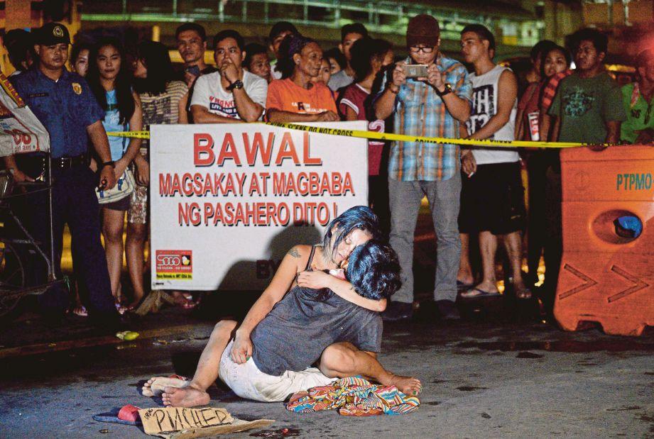 GAMBAR bertarikh 23 Julai 2016 ini menunjukkan seorang wanita memeluk mayat suaminya yang ditembak mati individu tidak dikenali di Manila. - AFP