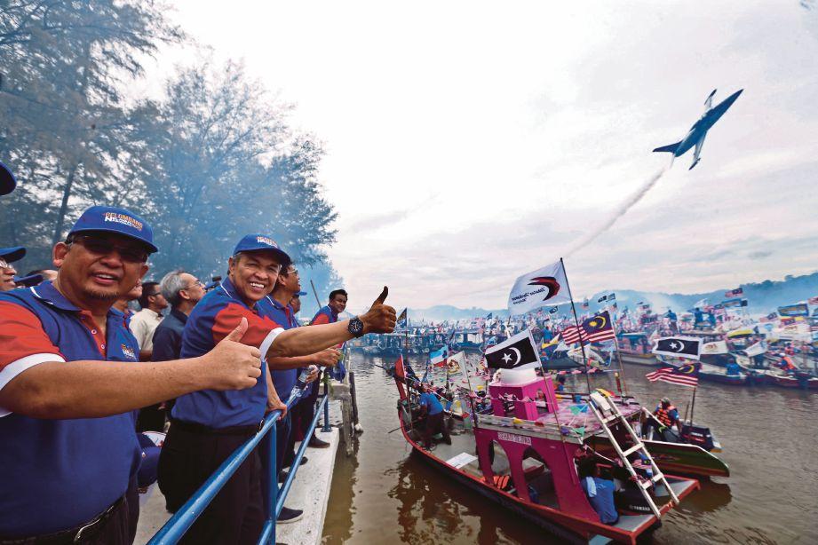 AHMAD  Zahid  (dua kiri)  dam Ahmad Razif  (kiri)  menyaksikan pertunjukan udara ketika merasmikan program Gelombang Nelayan Nasional di Jeti Kuala Kerteh, semalam.