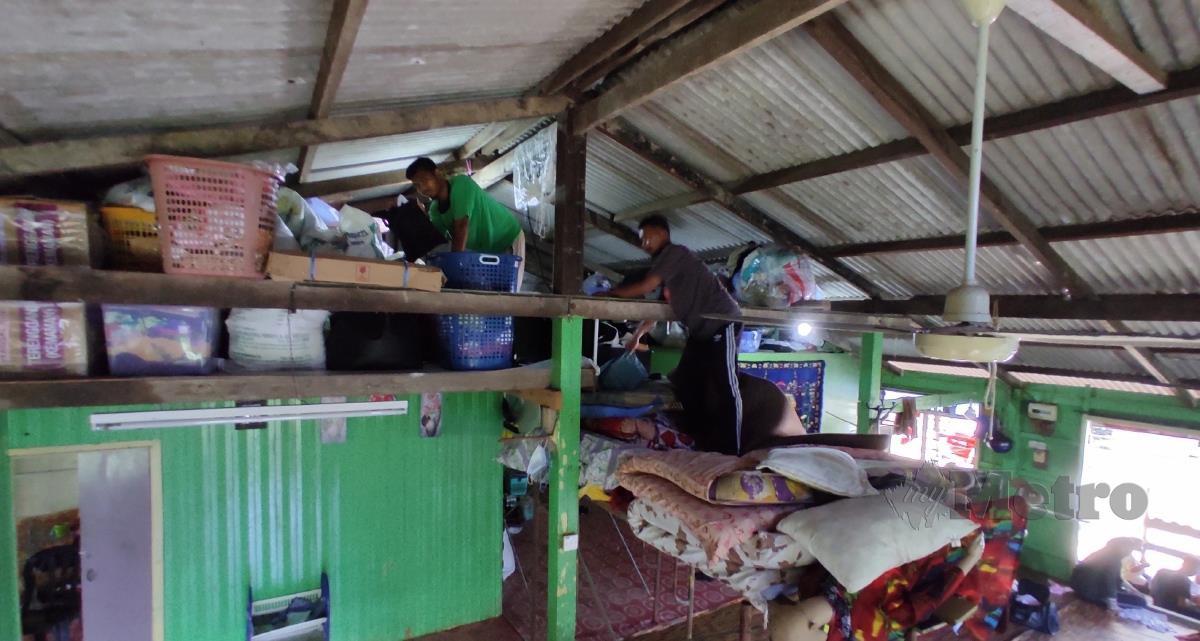 YUSOF bersama iparnya, Azizi mengambil barangan yang diperlukan yang disimpan di loteng bagi mengelak ditenggelami banjir. FOTO Zaid Salim
