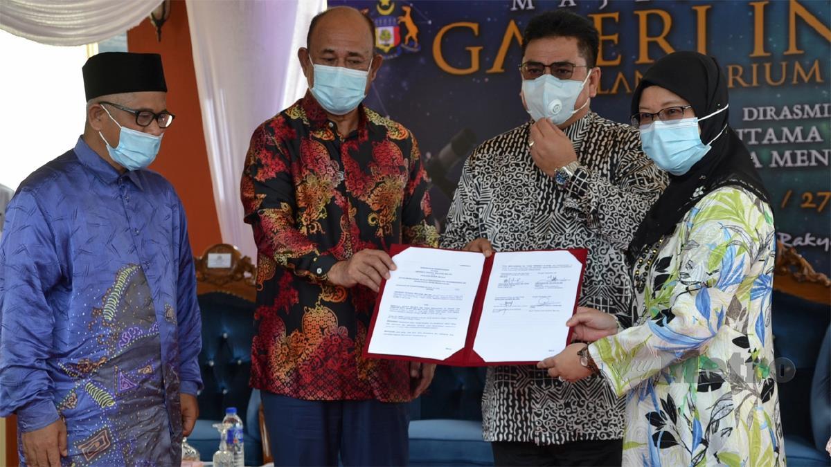 SULAIMAN menyerahkan memorandum Jabatan Mufti Melaka kepada Raha sambil diperhatikan Abdul Halim (kiri). FOTO Hassan Omar