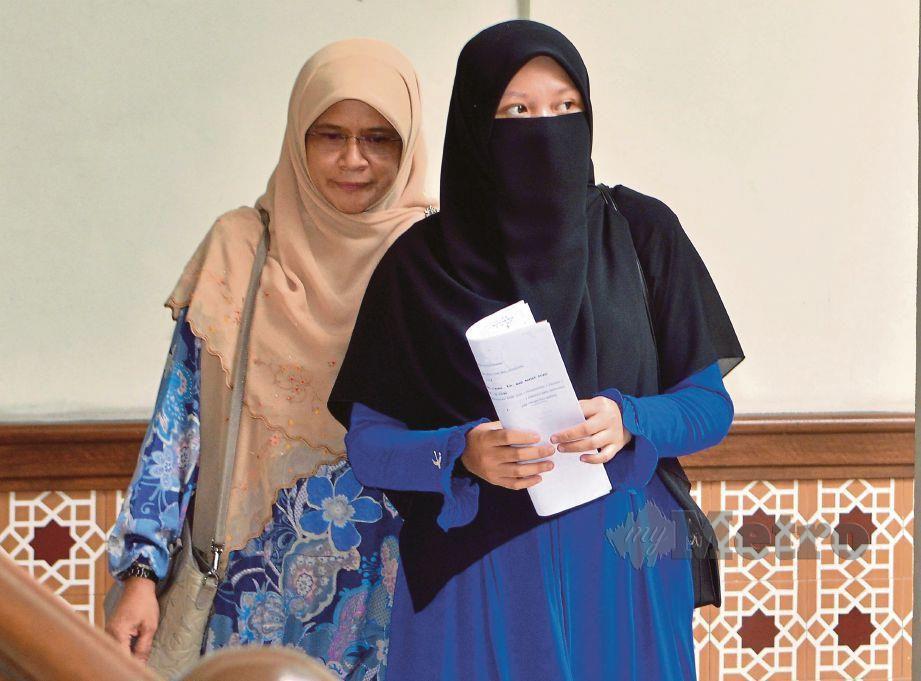 AIN 'Afini (kanan) ketika meninggalkan perkarangan mahkamah.