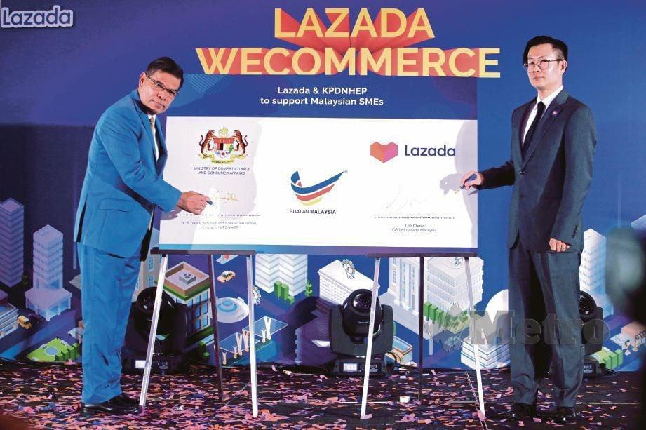 SAIFUDDIN  bersama Chow  menandatangani plak pada majlis perasmian Lazada Wecommerce 2019 Satellite Tradeshow, semalam.  FOTO  Khairul Helmy