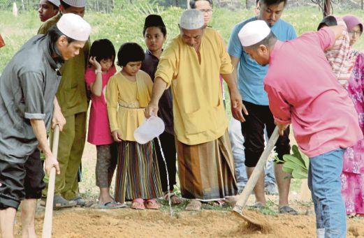 BAPA mangsa, Harikah Ahmad (tengah) menyiram air di pusara Nurul Hidayatul.