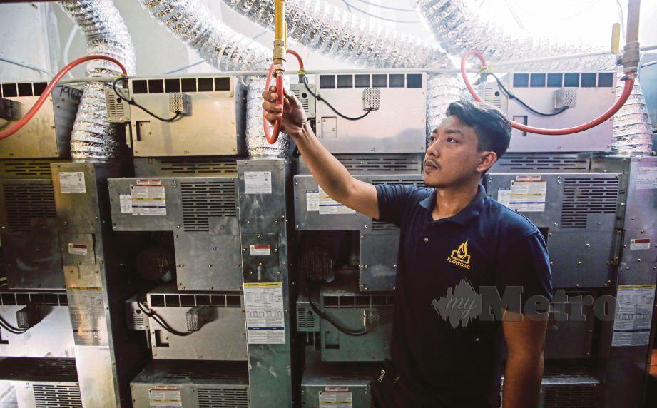 KONTRAKTOR pemasangan gas memeriksa saliran gas di sebuah  kedai dobi layan diri.