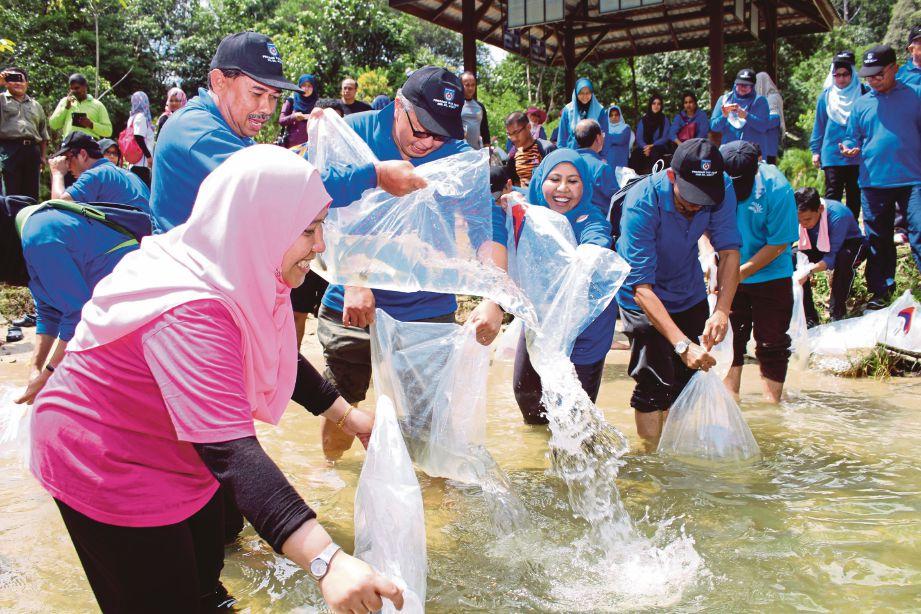 KAKITANGAN Jabatan Perikanan melepaskan benih ikan kelah ke dalam sungai.