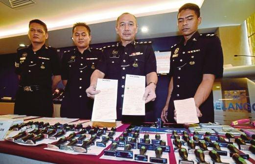 Mohd Sakri  (dua dari kanan) menunjukkan sijil cuti sakit palsu pada sidang media di Ibu Pejabat Polis Kontinjen (IPK) Selangor.