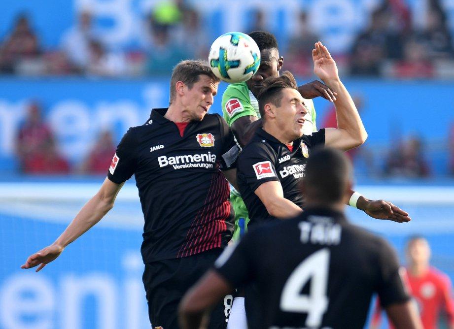PEMAIN tengah Leverkusen Lars Bender (kiri) dan Dominik Kohr (kanan) merampas bola daripada pemain  Wolfsburg,  Josuha Guilavogui.  FOTO/AFP