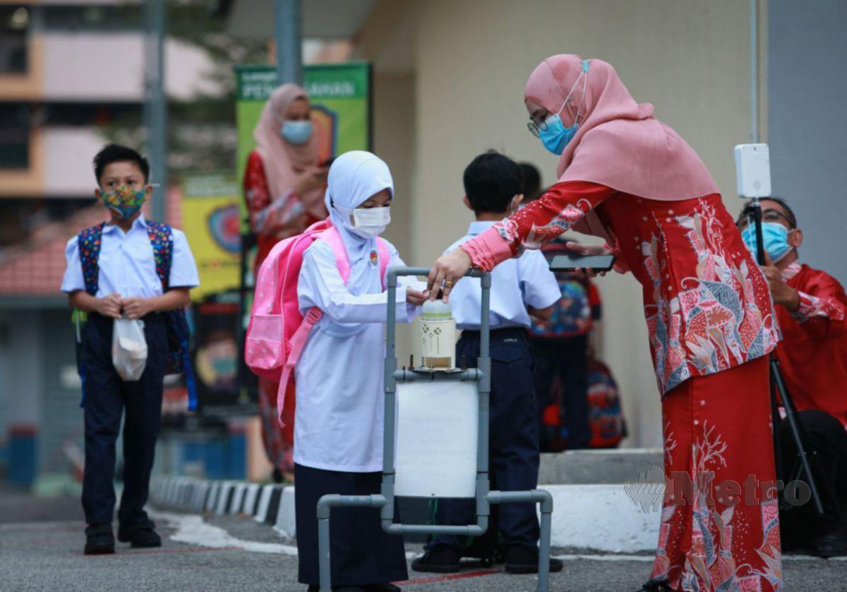 Guru membantu murid menggunakan cecair pembasmi kuman ketika pembukaan sekolah pada 1 Mac 2021. FOTO Aswadi Alias.