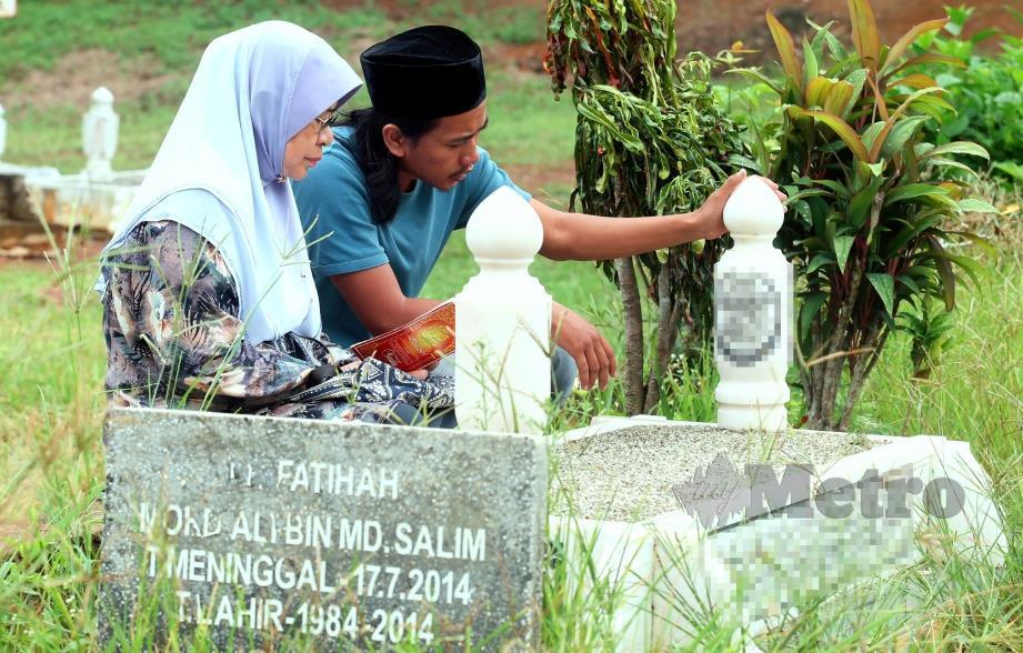 JUNAIDAH bersama Mohd Salman menziarahi pusara Allahyarham Mohd Ali di Tanah Perkuburan Islam Kampung Raja, Pagoh.