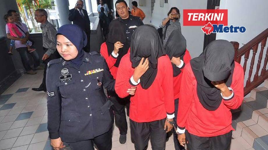 TERUTUDH diiringi anggota polis ketika dihadapkan di Mahkamah Sesyen Ayer Keroh. FOTO Muhammad Hatim Ab Manan