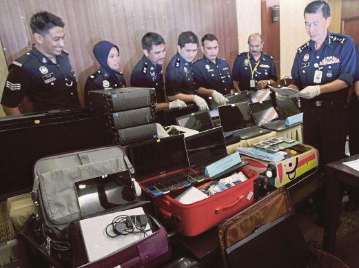 LAW (kanan) melihat barang rampasan sindiket Macau Scam selepas sidang media di IPK Kuala Lumpur.