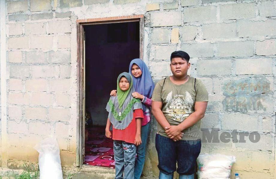 MOHAMAD Syahadam bersama dua adiknya yang tinggal di rumah serba kekurangan tanpa air dan elektrik. FOTO Ramli Ibrahim