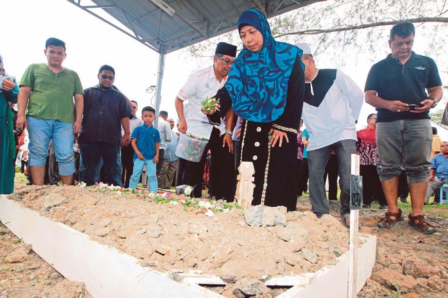 Noorlida menyiram air mawar di pusara suami di Tanah Perkuburan Bukit Mahkota, semalam. Gambar kecil, Abd Rahim.