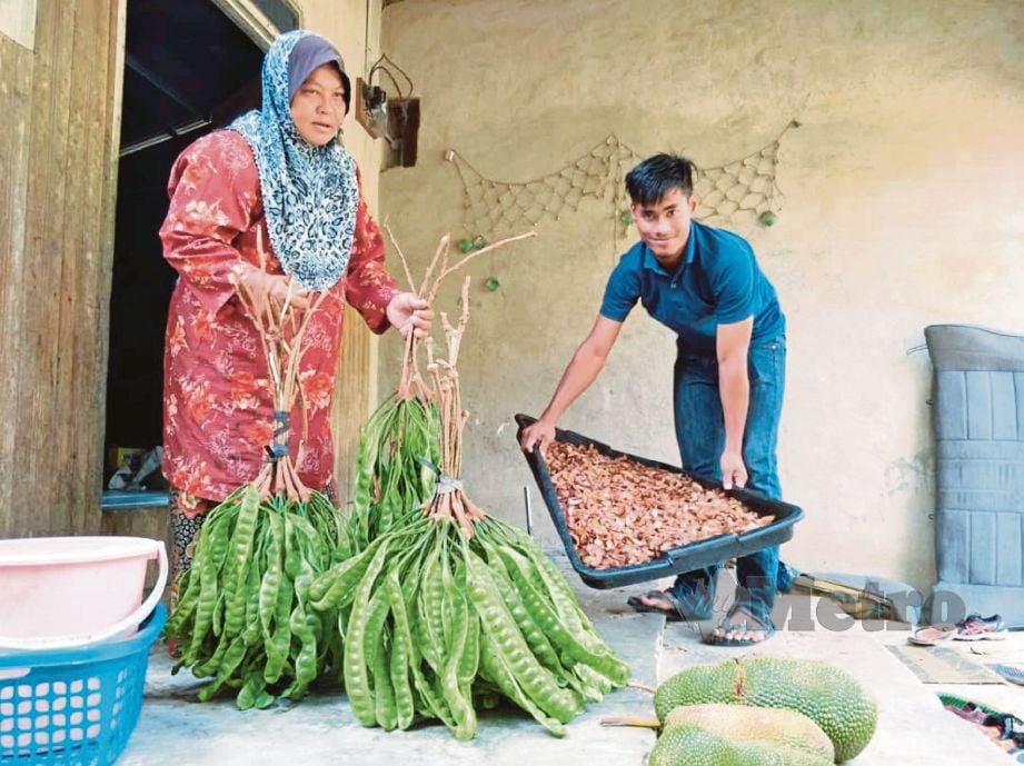 MUHAMMAD Izzat Amran membantu ibunya menjaja petai dan asam gelugor bagi menambah pendapatan keluarga.