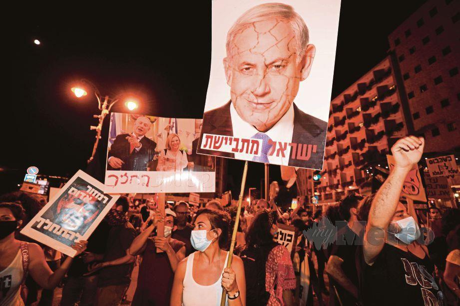 SEORANG wanita membawa sepanduk   ketika menyertai acara tunjuk perasaan  di kediaman peribadi Netanyahu di bandar utara Caesarea.