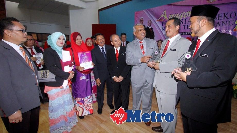 SHAFRUDDIN Ali (tiga kanan) dan Ketua Penolong Pengarah Bahagian Teknologi Pendidikan Negeri Terengganu, Alias Talib (empat kanan) beramah mesra dengan pemenang Penggunaan Bahan Digital MBMMBI Terbaik kategori sekolah rendah dan menengah. FOTO Mohd Syafiq Ridzuan Ambak