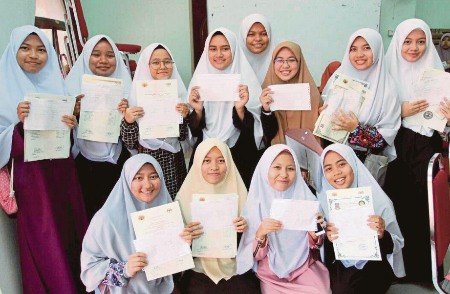 Sebahagian pelajar menunjukkan keputusan Sijil Tinggi Agama Malaysia selepas diumumkan di Dewan Sekolah Maahad Muhammadi Perempuan di Jalan Merbau, Kota Bharu, semalam.