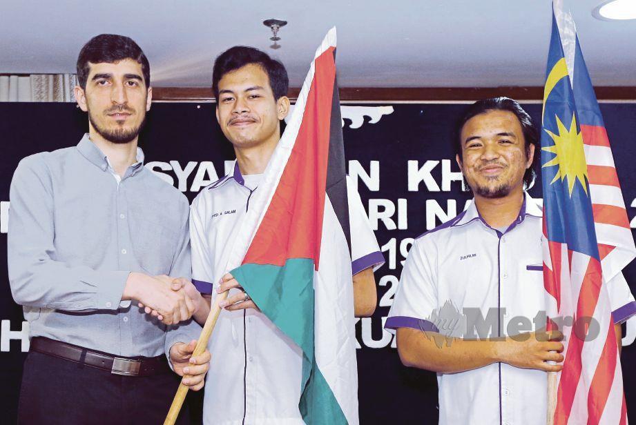 MUSLIM (kiri) bertukar bendera dengan Naib Presiden GAMIS Syed Ahmad Abdus Salam Syed Nazmi (tengah), semalam. FOTO Nadim Bokhari