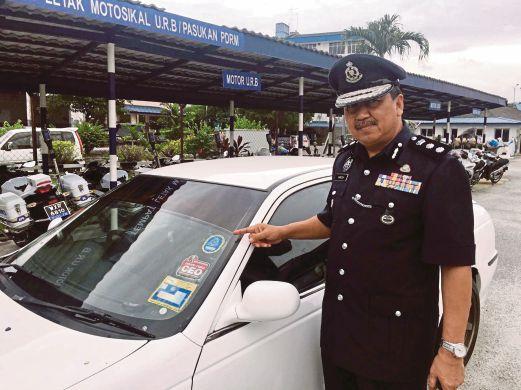 HAMZAH menunjukkan pelekat lambang polis yang ditampal pada kereta suspek dipercayai digunakan untuk penyamaran.