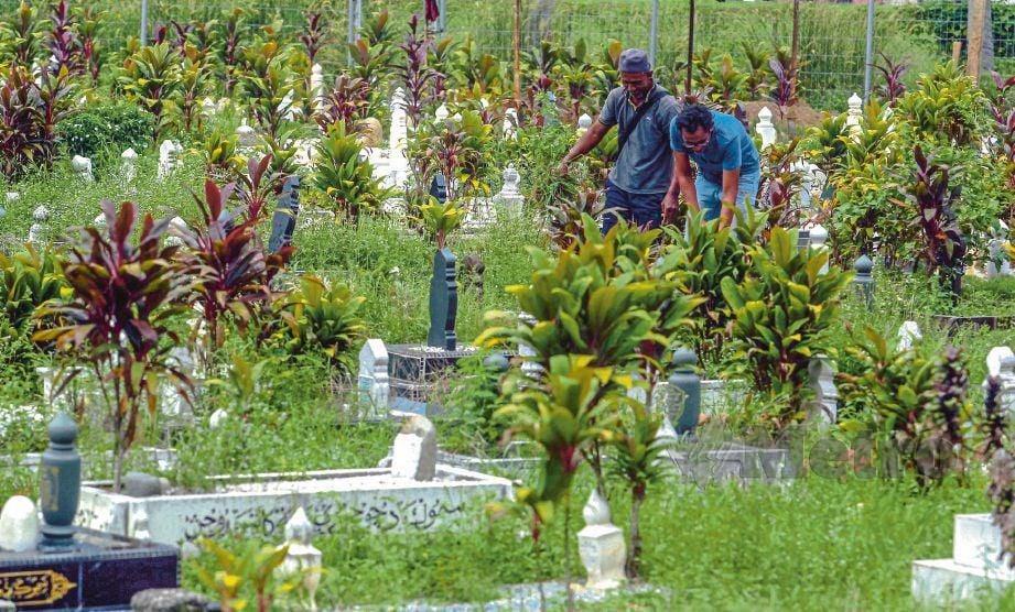 MOHAMAD Rashidi  (kanan) dan rakannya, Mohd Nizam Ahmad, 49,  membuat pembersihan di Tanah Perkuburan Islam Sungai Kantan, Kajang.