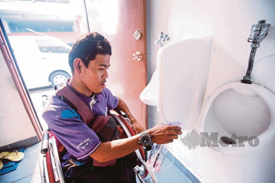 MUHAMMAD Helmi pencuci tandas awam di Puchong. FOTO Syarafiq Abd Samad