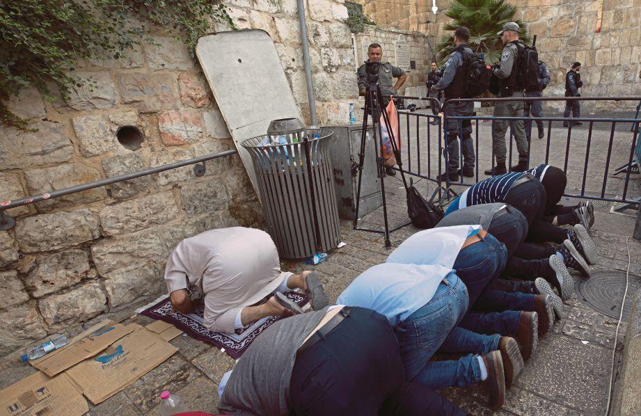SEKUMPULAN lelaki menunaikan solat di sebelah Pintu Singa selepas enggan melalui peralatan keselamatan yang diletakkan di laluan masuk ke pekarangan Masjid Al-Aqsa. - EPA