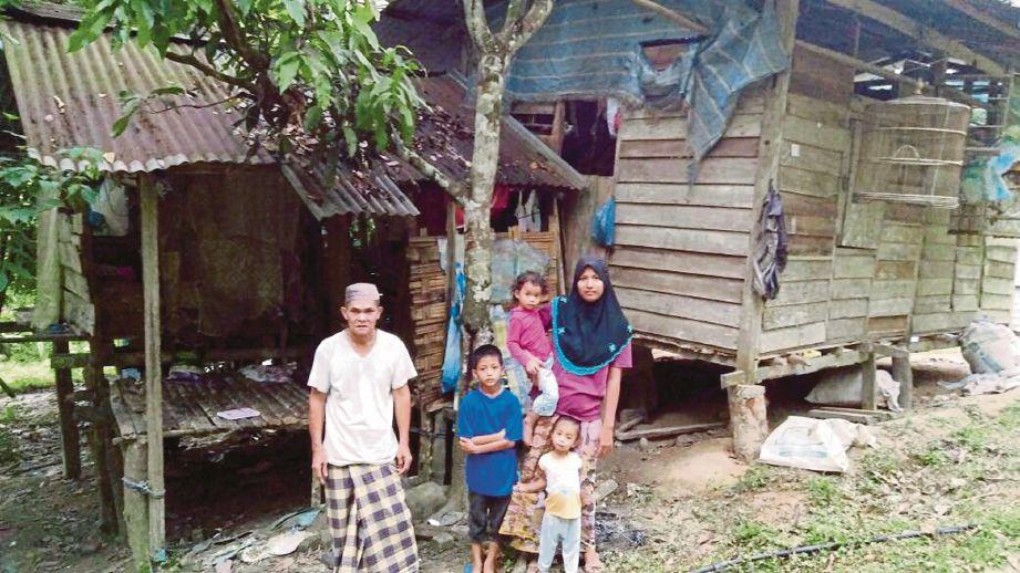 ZAKARIA  (kiri) bersama ahli keluarganya di hadapan rumah mereka di Kampung Padang Cik Mas, Pulai.